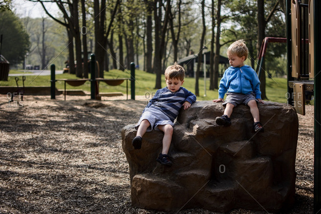 Brothers sitting on rock in playground