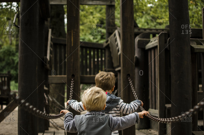 Rear view of brothers holding chain against jungle gym in playground