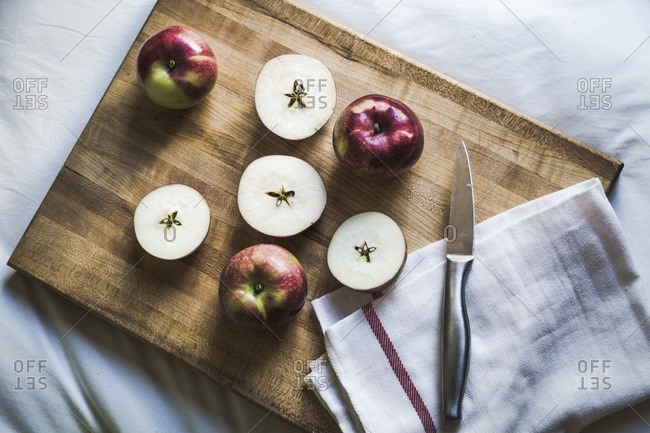 High angle view of apple with kitchen knife and napkin on cutting board