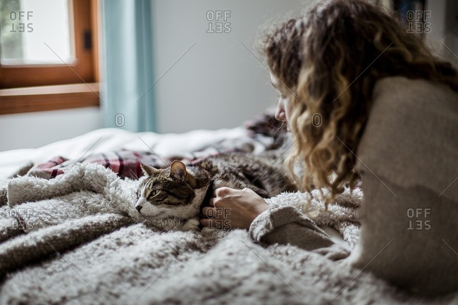 Woman playing with cat while lying on bed at home
