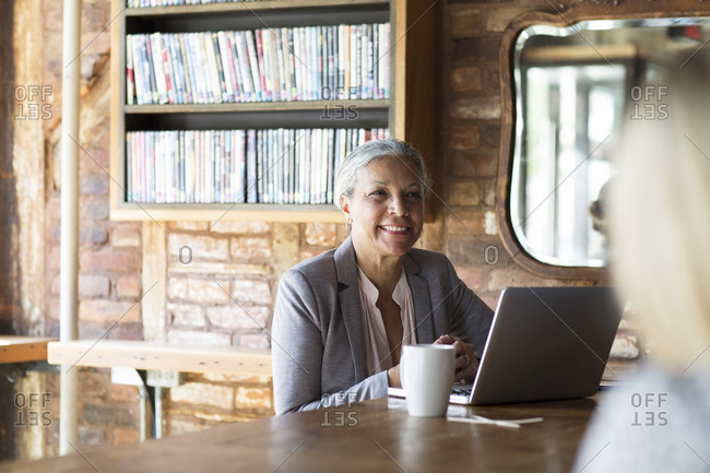 Smiling woman using laptop while sitting by bookshelf at cafe