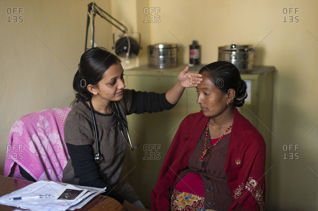 A General Practitioner consults a patient and checks her temperature at hospital in Nepal