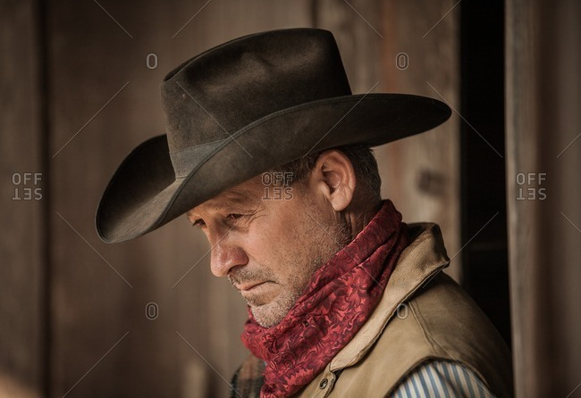 Portrait of a cowboy with hat and red scarf in front of a rustic barn