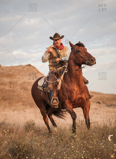 A cowboy on horseback riding on a rugged hill