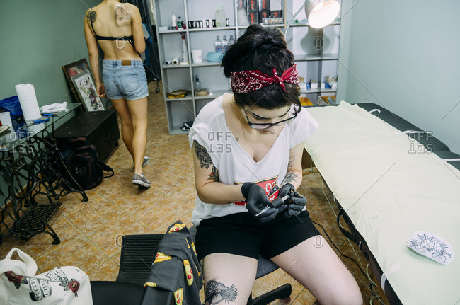 Stylish hipster tattoo artist tattooing a woman in her studio