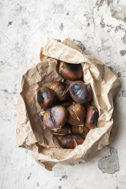 Roasted chestnuts in craft paper bag on white rustic background