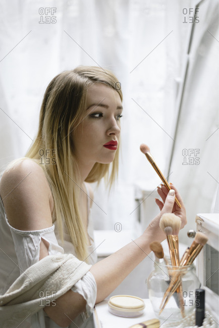 Beautiful young woman looking at vintage mirror and applying makeup