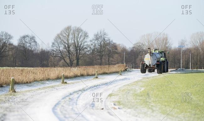 Fertilizing tractor on frozen road in rural winter landscape