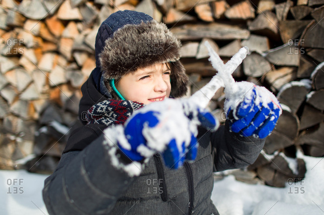 Child dressed warm in front of a pile of logs looking through crossed icicles into sun