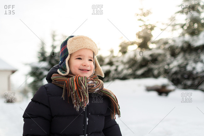 Smiling child wearing ear flaps and a scarf enjoying snowy day