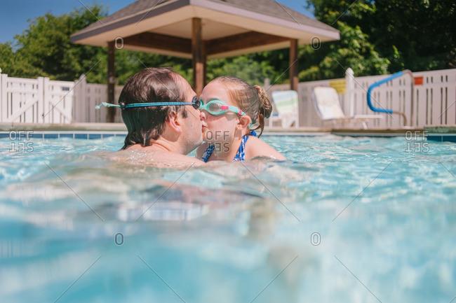 Man kissing daughter in pool