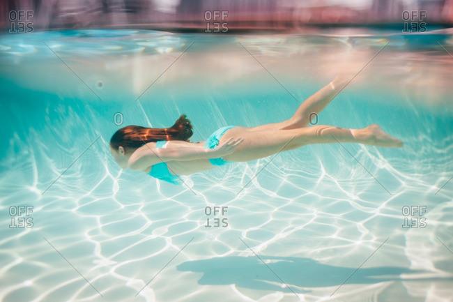 Girl swimming underwater in pool