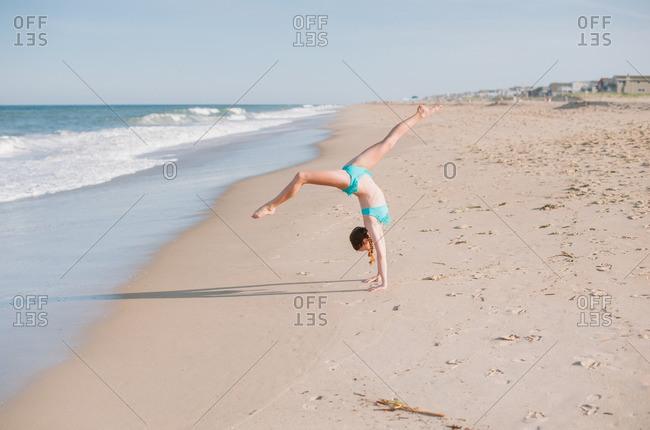 Girl doing flip on beach