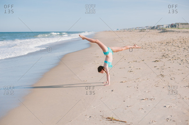 Girl doing handstand on beach