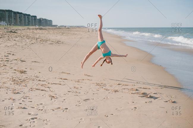 Girl doing a flip on beach