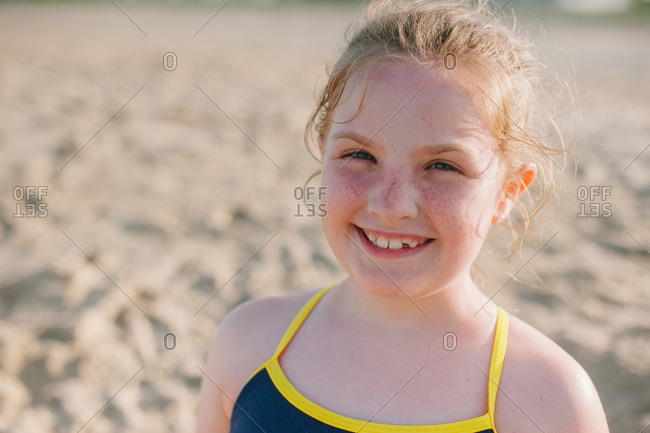 Smiling girl with freckles on a beach