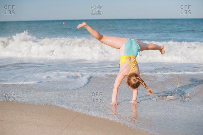 Girl doing cartwheel on the beach