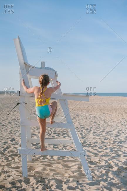 Girl climbing beach lifeguard chair