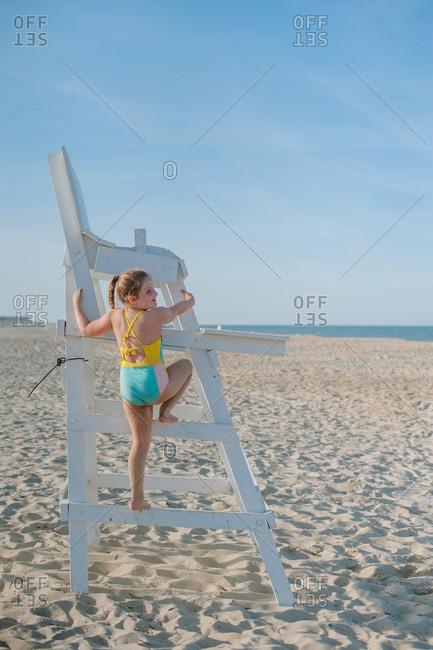 Girl climbing a beach lifeguard chair