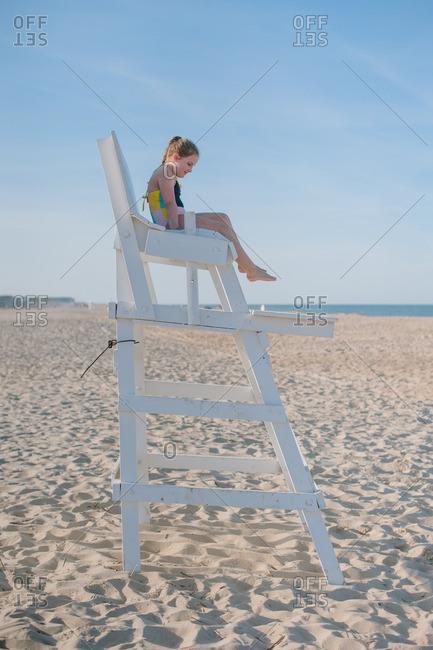 Girl sitting in beach lifeguard chair