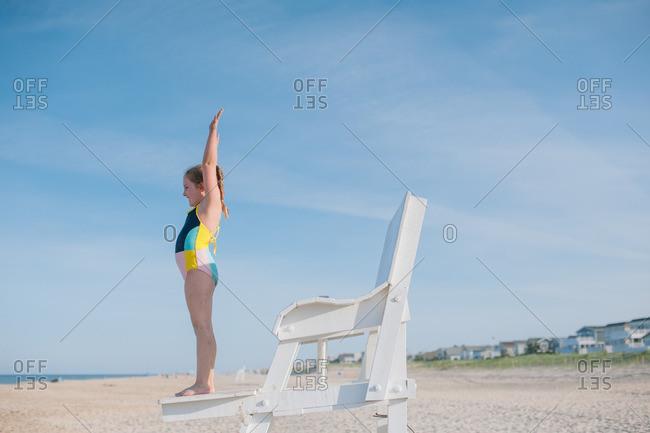 Girl standing on beach lifeguard chair
