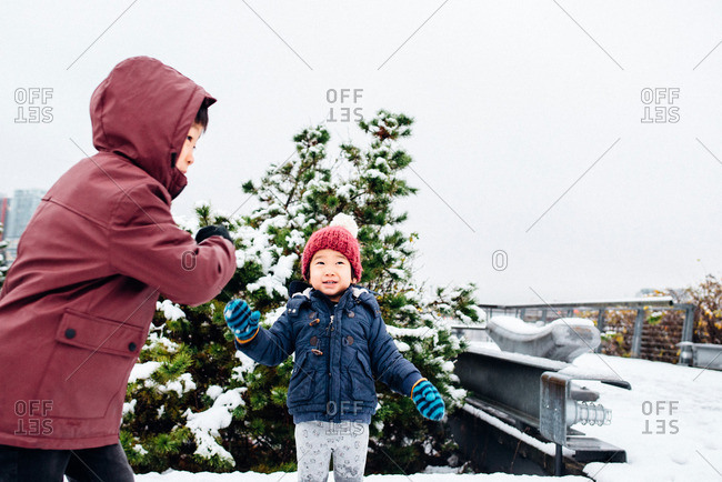 Two boys bundled up outside in the snow
