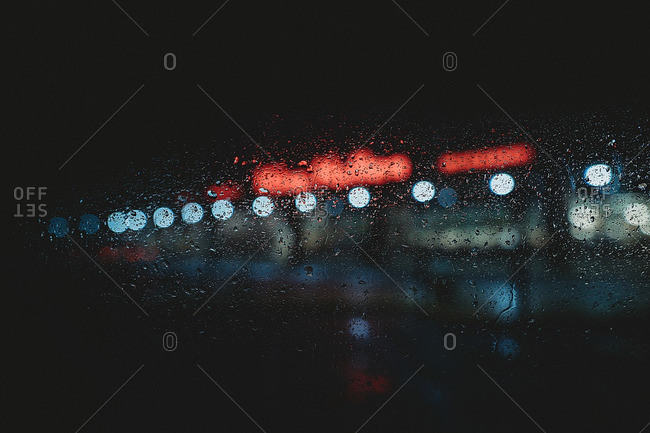 Burred lights on a rainy night through a window covered with raindrops