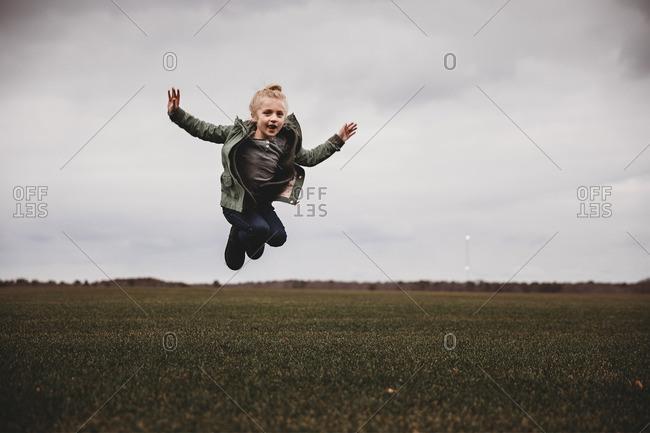 Girl in midair jump above a field