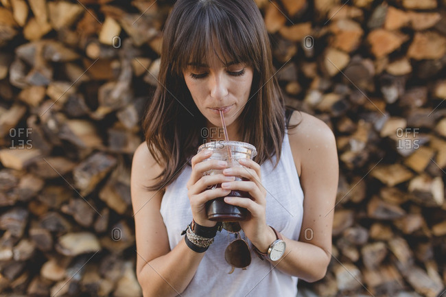 Casual young woman drinking iced coffee