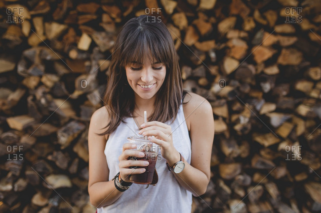 Smiling young woman drinking iced coffee