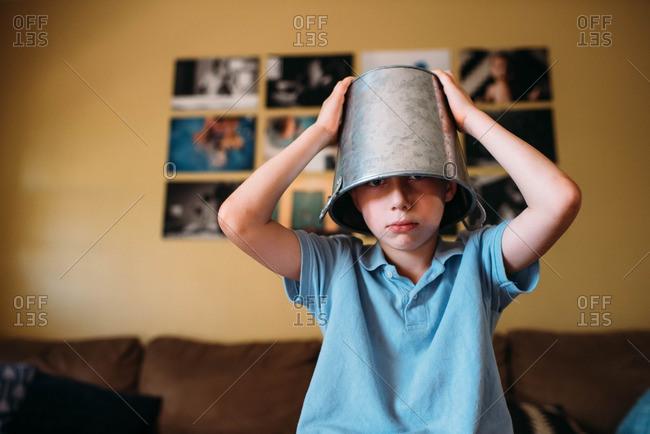 Boy wearing a silver bucket on his head