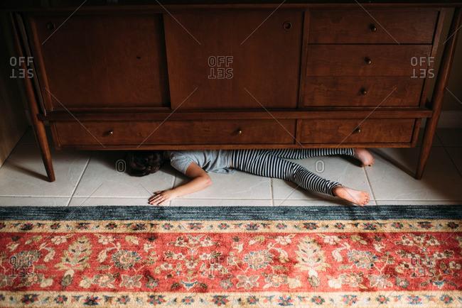 young girl hiding under a midcentury credenza