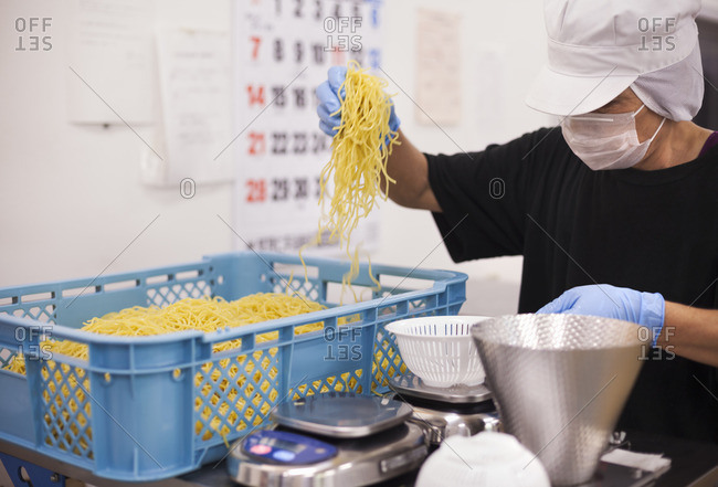 Workers in aprons and gloves weighing and packing freshly made noodles in a soba noodle production unit.