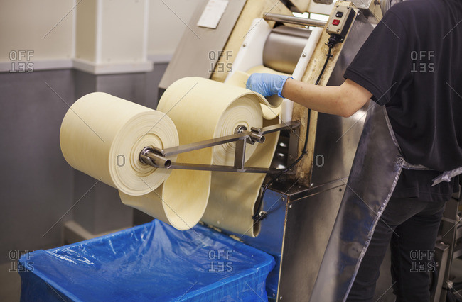 A Soba noodle factory.  Sheets of fresh noodle dough being passed through a large pressing machine.