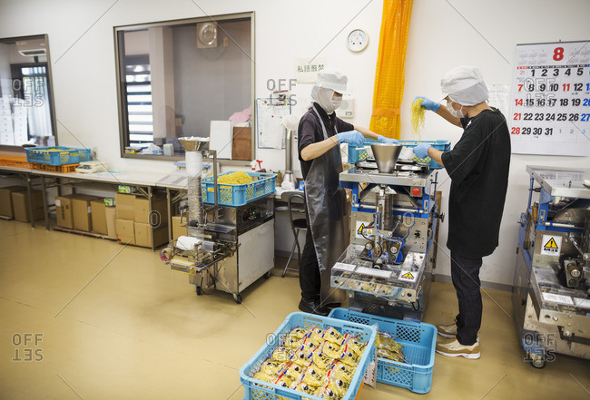 Japan - August 4, 2016: Workers in a factory producing Soba noodles . Two men mixing noodle dough in a machine.