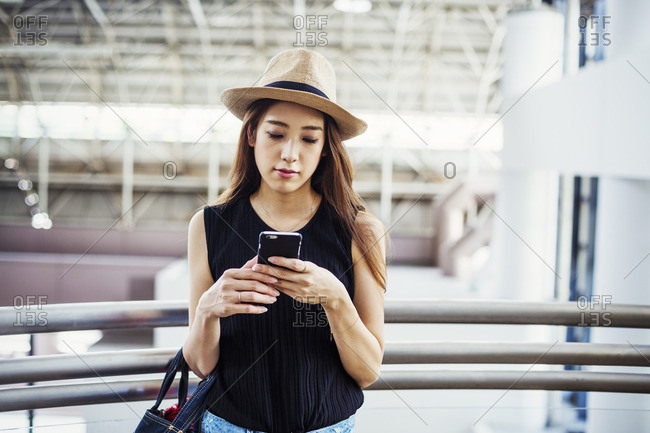 Young woman with long brown hair, wearing a Panama hat, in a shopping center, using a mobile phone.