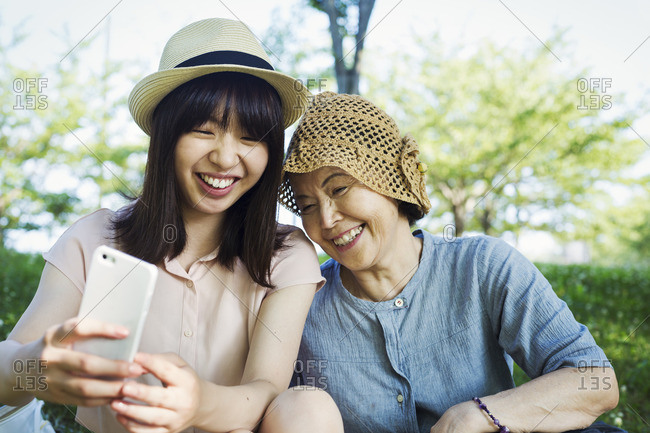 Portrait of a smiling senior woman wearing a crochet hat and a young woman wearing a panama hat.