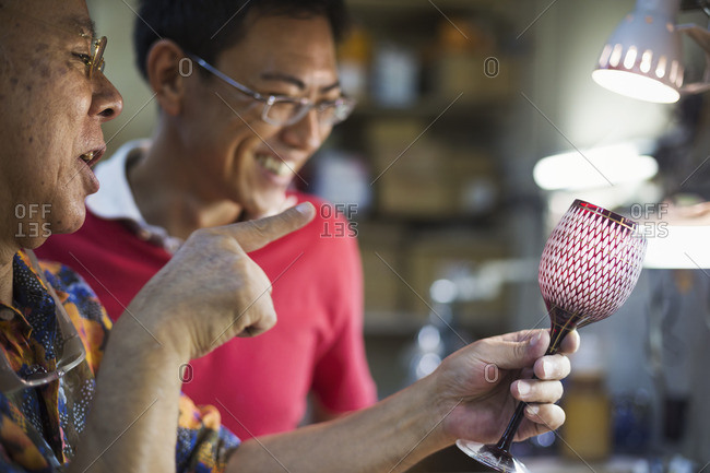 Father and son at work at a glass maker's studio workshop, inspecting a red cut glass wine glass.