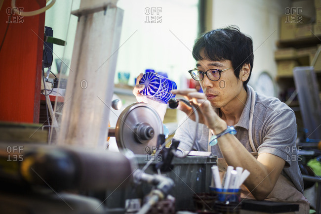 A craftsman at work in a glass maker's workshop polishing a vivid blue cut glass object.