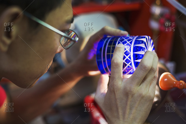 A craftsman glass maker holding a vivid blue cut glass cup, inspecting it closely.