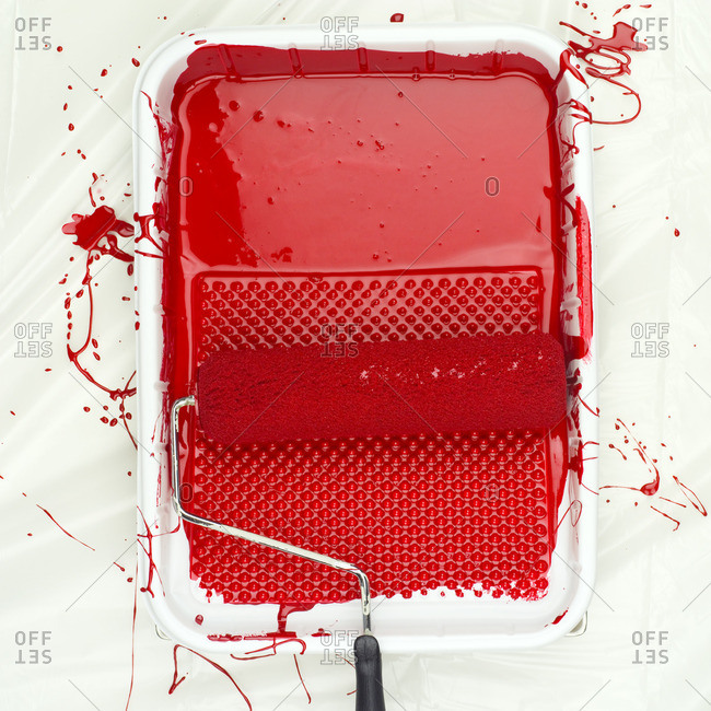 Paint roller on tray with red paint