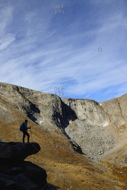 USA, Colorado, Silhouette of hiker on rock ledge along Chicago Lakes Trail in Mount Evans Wilderness Area