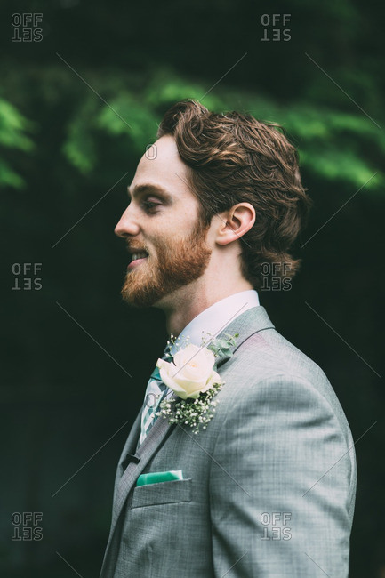 Profile view of groom in a gray tux