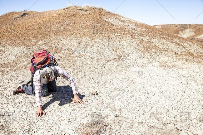 Man studying soil in arid setting