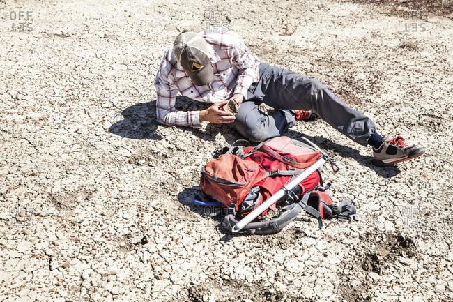 Man holding piece of arid soil