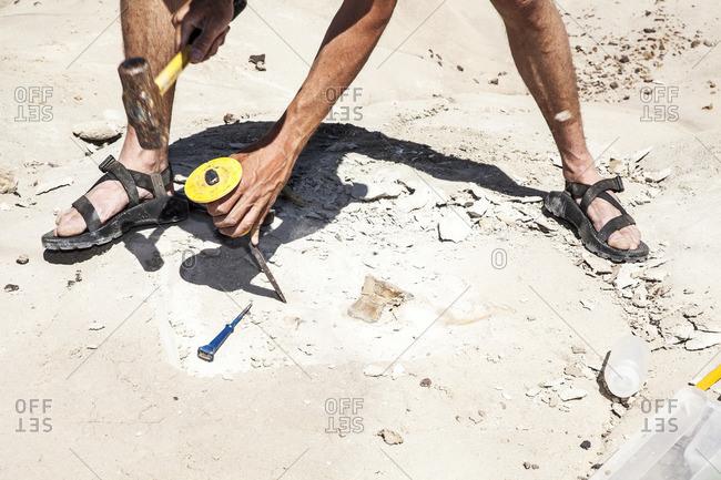Paleontologist using tools in arid ground