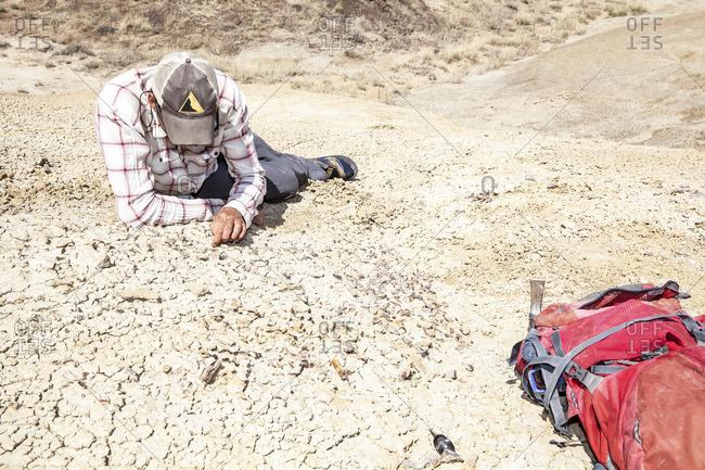 A man examining soil in desert