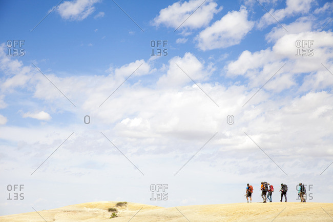 People trekking in a desert setting