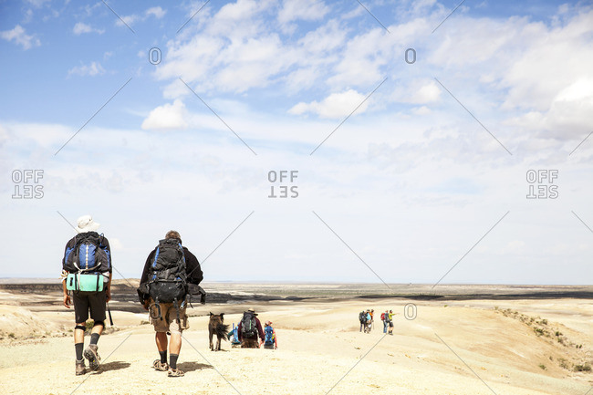 People trekking in desert with backpacks