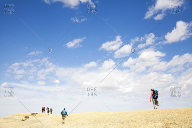 People trekking in desert setting